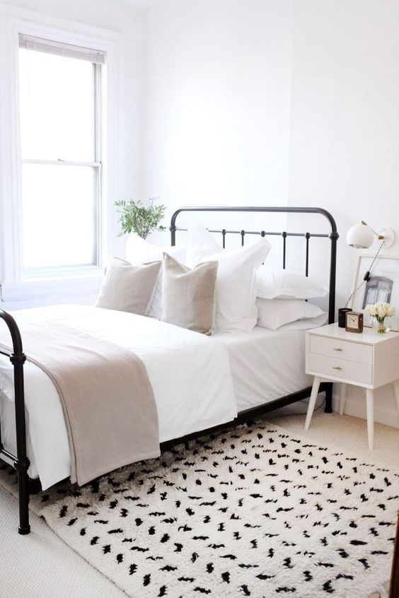 black metal bed frame in white bedroom