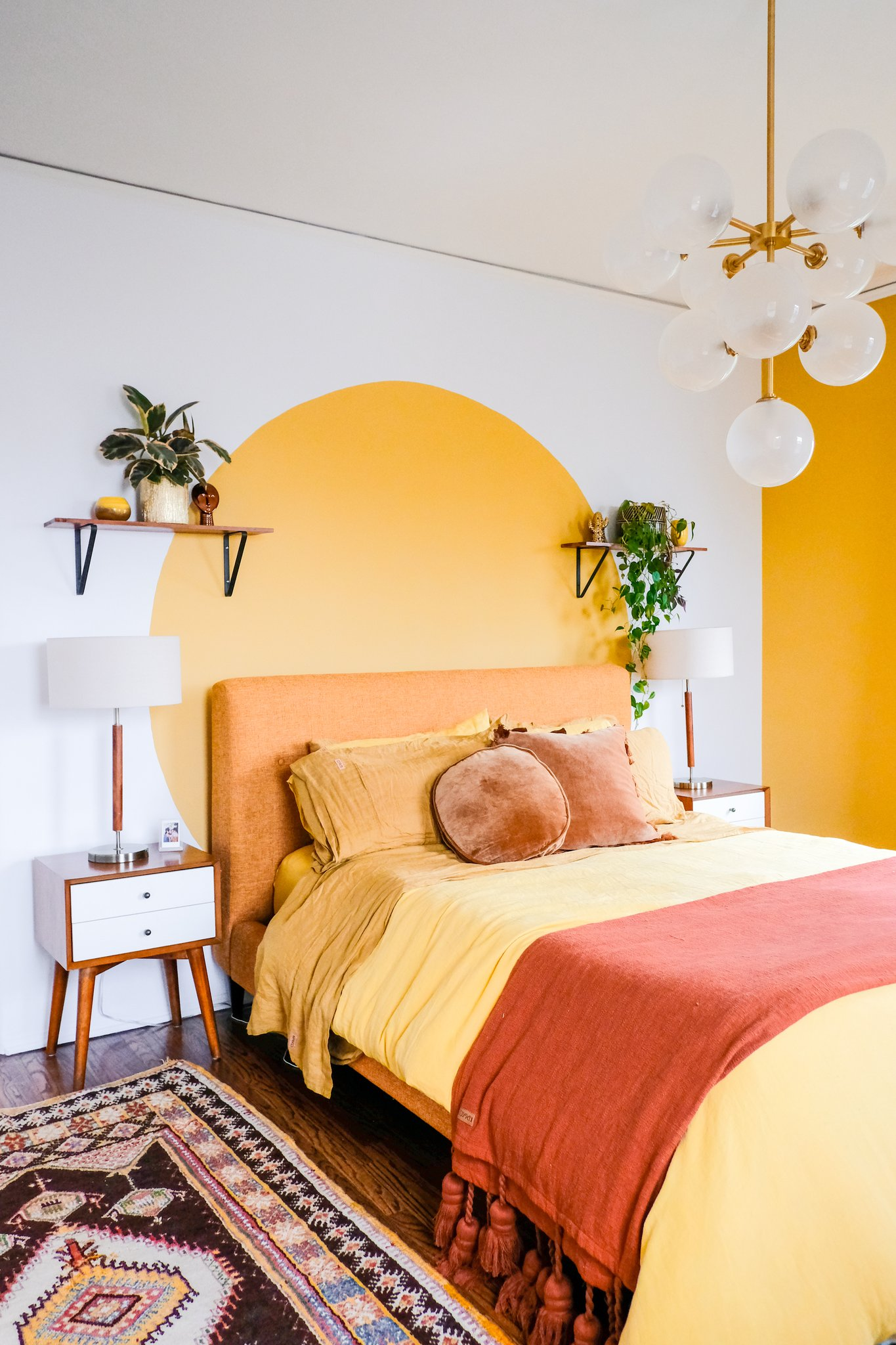 yellow orange blush and red bedroom design with indoor greenery and paint feature