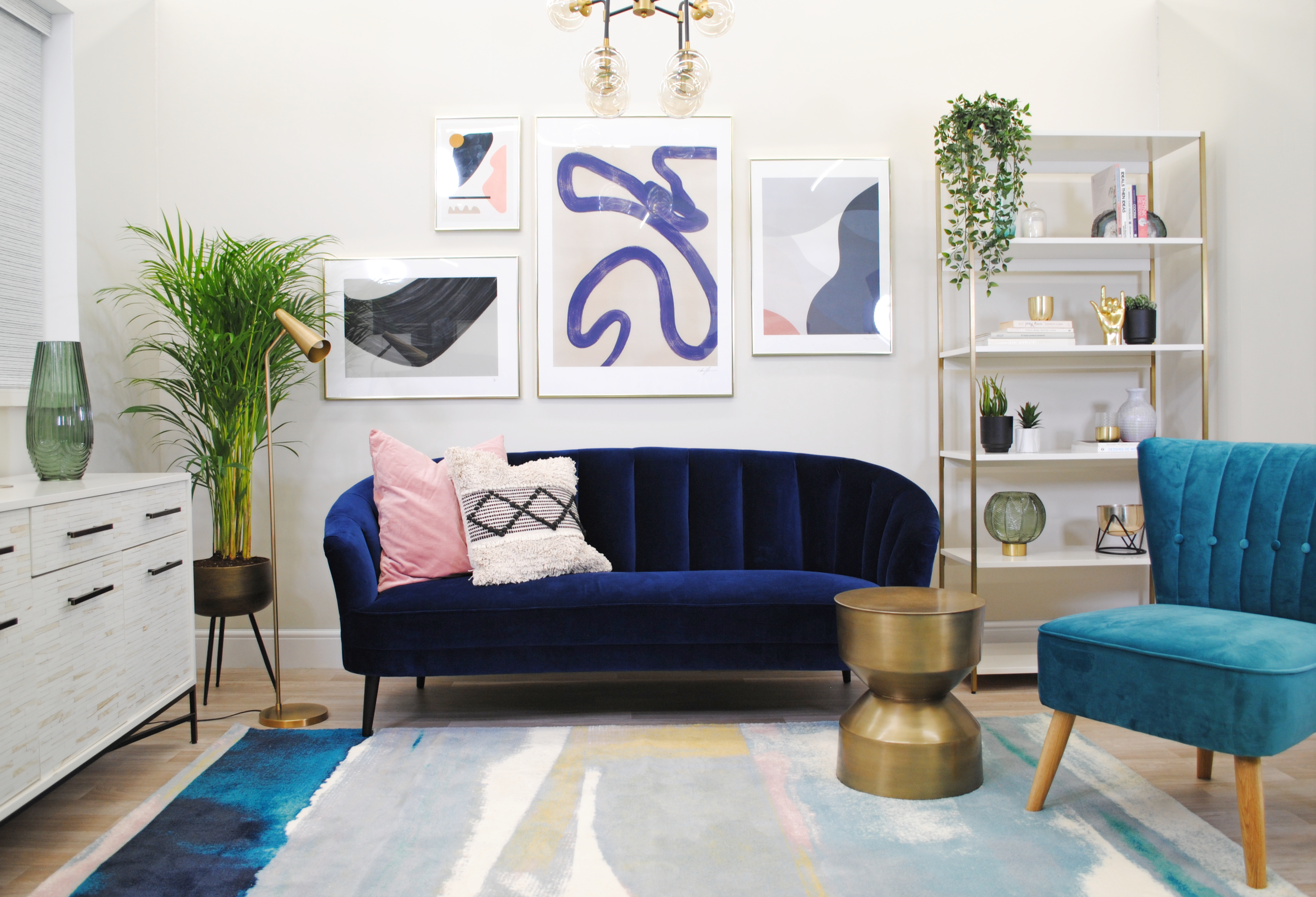 living room with navy sofa and blue occasional chair and gallery wall