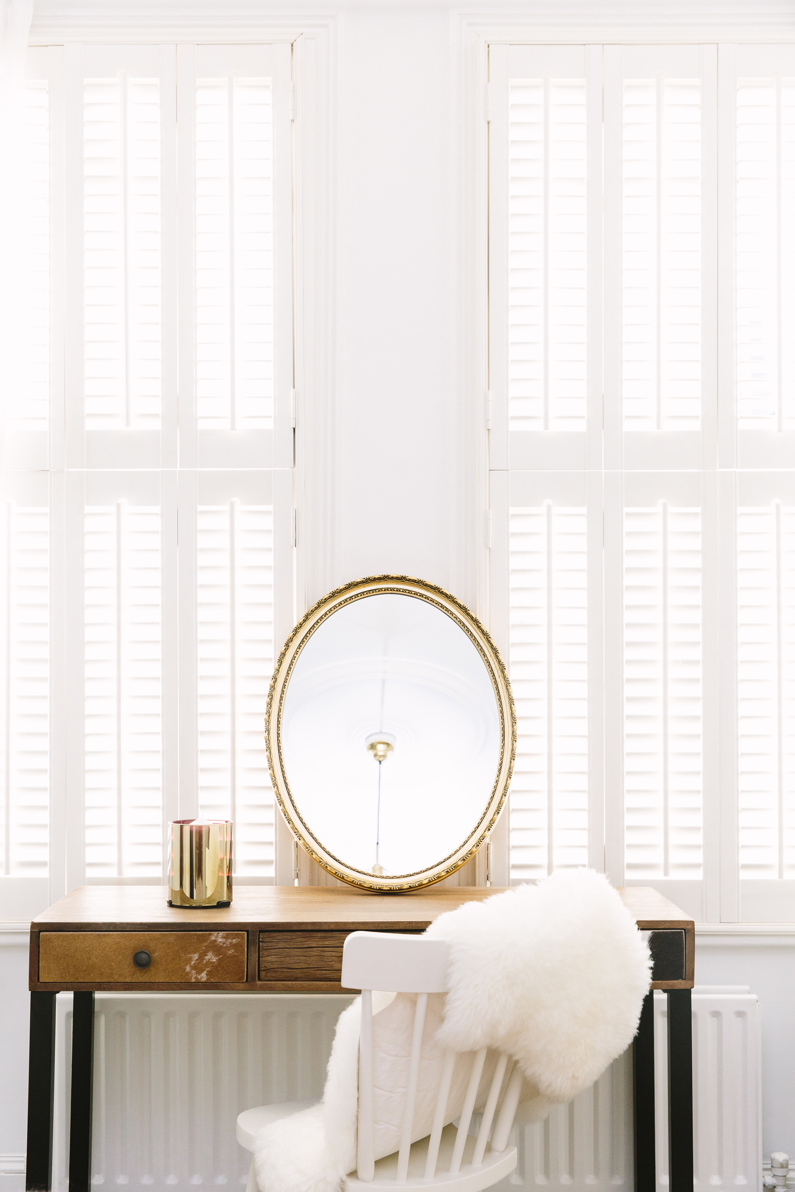 bedroom dining table with brass mirror and faux sheepskin white shutters