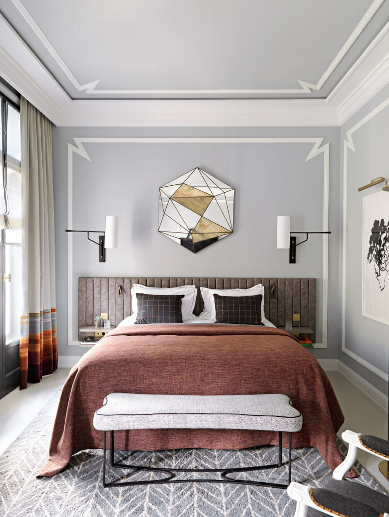 master bedroom with feature headboard statement mirror and wall panelling