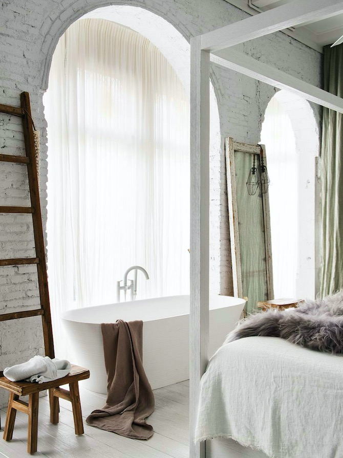 bath in bedroom with rustic finishes and exposed brick
