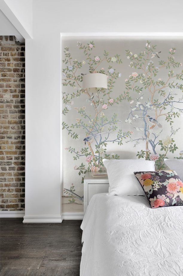 bedroom with floral feature wall paper exposed brick wall and decorative cushions and wall lights