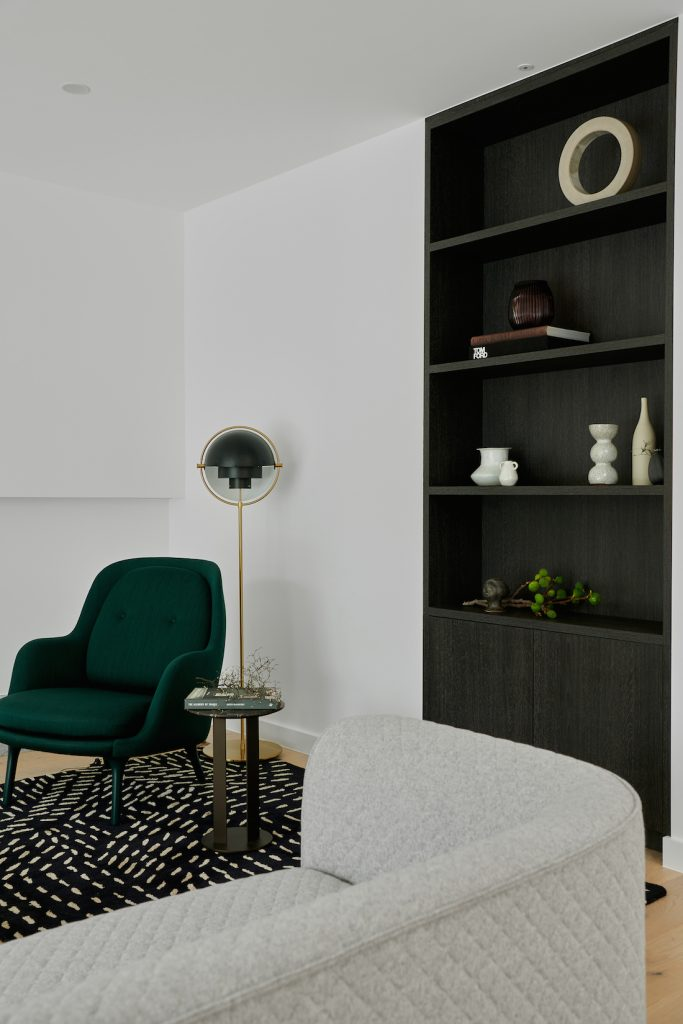 Lounge-room-with-green-velvet-chair-and-black-veneer-bookcase-683x1024