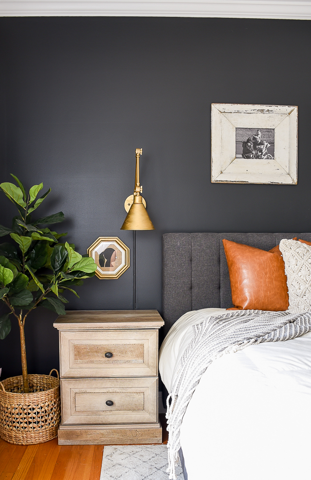 dark statement wall in bedroom with brass accents and traditional elements