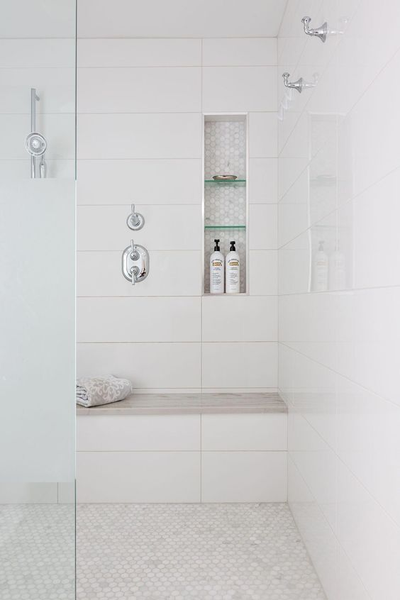 white shower with seat and small hexagonal floor tiles