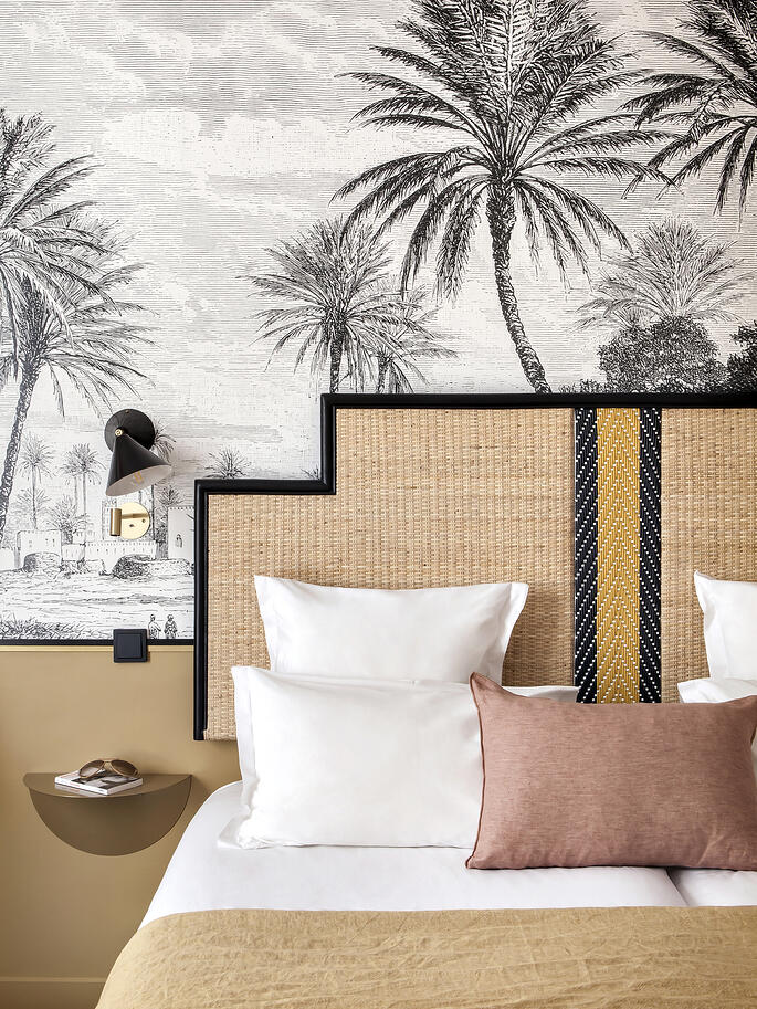 hotel-doisy-woven-headboard-and-black-and-white-tropical-mural-wallpaper-via-coco-kelley