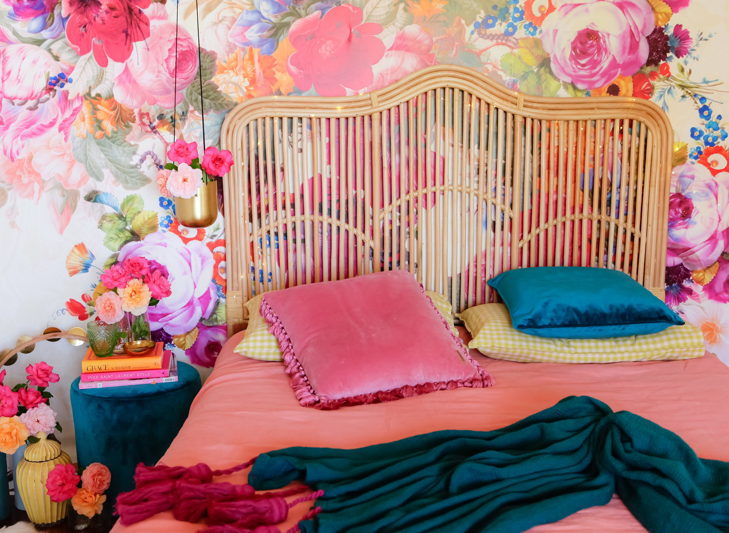 brightly coloured bedroom with wood bamboo rattan headboard velvet and floral wall mural
