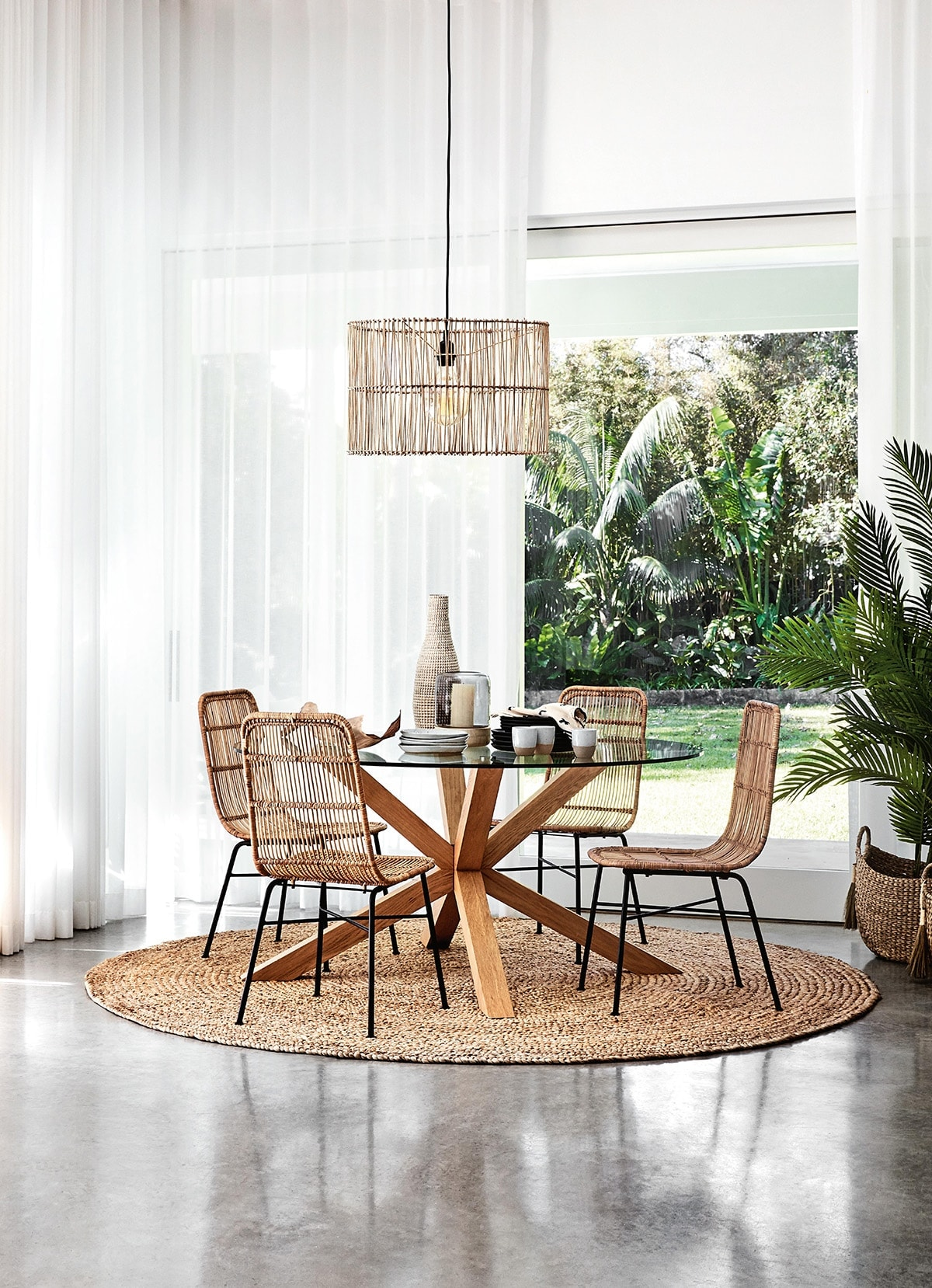 round-jute-rug-under-glass-dining-table-from-freedom-with-coastal-dining-chairs
