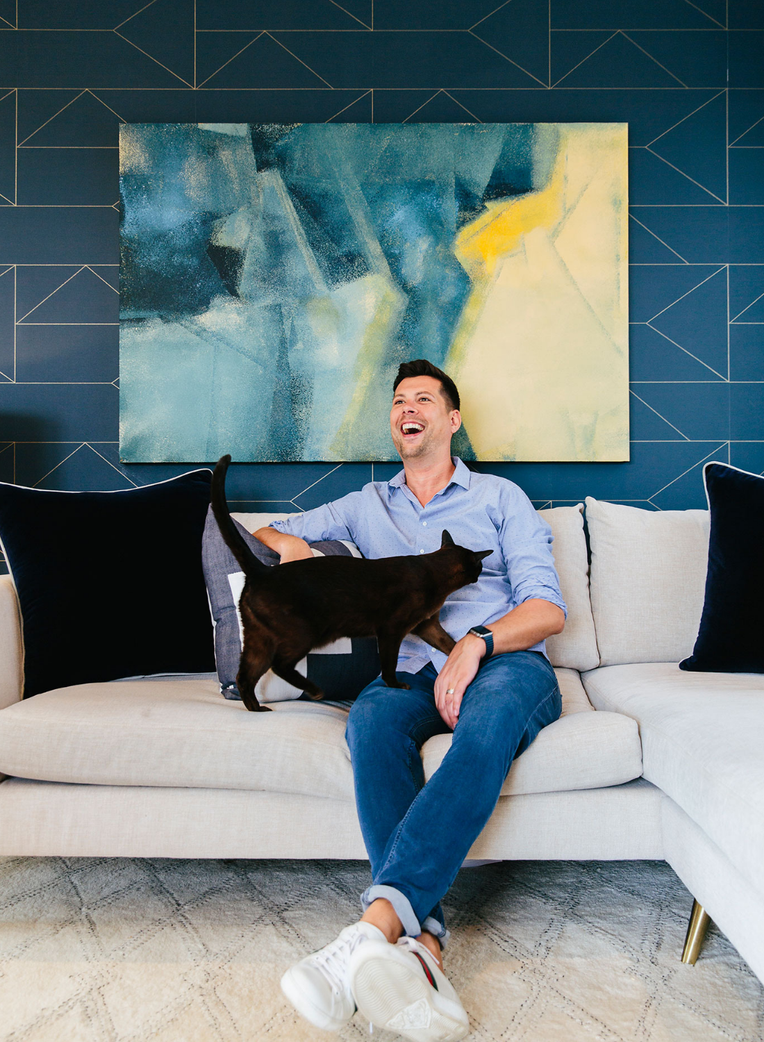 Happy home man laughing with cat in interior designed london flat